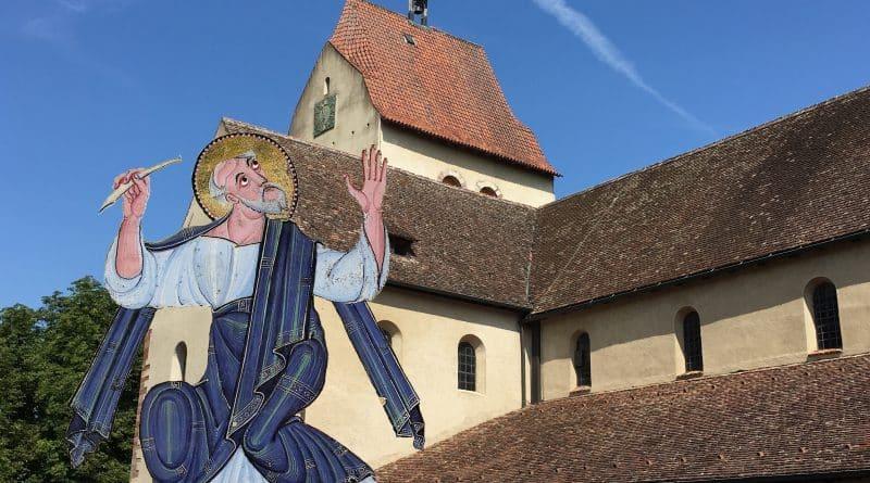 Evangelist Markus, aus dem sog. (Bamberger) Evangeliar Heinrichs II. (um 1000) vor einem Foto des Münsters St. Maria und Markus, Mittelzell Reichenau